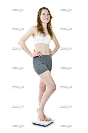 Happy young girl standing on bathroom scale