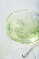 Martini cocktail with ice and slice of lime on marble table background. Alcoholic cocktail or non-alcoholic mocktail.