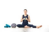 Restorative yoga with a bolster. Young sporty female yoga instructor in bright white yoga studio, smiling cheerfully while preparing restorative yoga exercise props