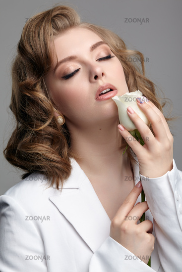 Woman in white jacket with eyes closed and hand with white rose flower near face.