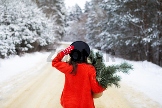 A girl in a red sweater and hat stands in the middle of a snowy road in a forest with pine branches. Weekend trip.