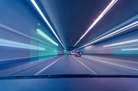 Driving fast through a city underground with blurry lights effect as a concept for high speed transportation and connectivity.