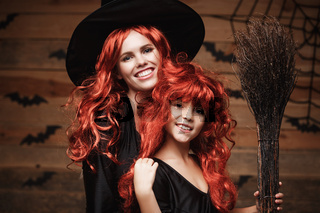 Beautiful caucasian mother and her daughter with long red hair in witch costumes celebrating Halloween posing with over bats and spider web on Wooden studio background.