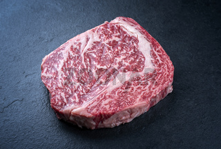 Raw dry aged wagyu cutlet steak cut offered as close-up on black background with copy space