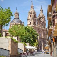Old street in Salamanca with La Clerecia Church