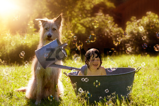 Dog showers toddler with watering can and soap bubbles