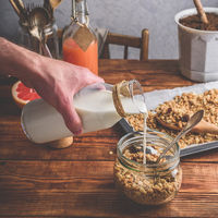 Man pouring milk on cereals