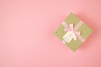 Golden box with ribbon lying on pink background with copy space