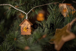 Winter time view of christmas tree garland in the form of small houses and golden star.