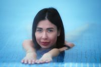 Beauty brunette woman lies and relaxes in mineral water in pool at spa