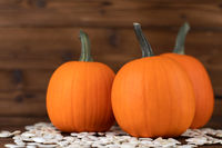 Pumpkins and seeds on wooden backdrop