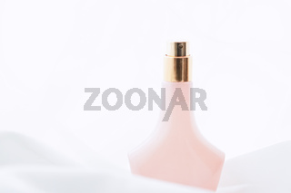 Vintage pink and gold perfume bottle and white silk, beauty and cosmetic