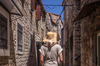 Beautiful blonde young female traveler wearing straw sun hat sightseeing and enjoying summer vacation in an old traditional costal town at Adriatic cost, Croatia