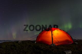 Nordlicht (Aurora borealis) ueber einem erleuchteten Zelt, Moere und Romsdal, Norwegen