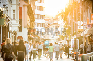 Blurred crowd of people on Copova pedestrian street in Ljubljana at sunset. Urban lifestyle and mobility concept.