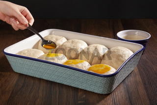 Fresh buns with yolk in a ceramic oven tray ready to bake.