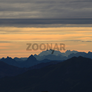 Bright lit yellow morning sky over Mount Grosser Mythen, Saentis and other mountains in the Swiss Alps.