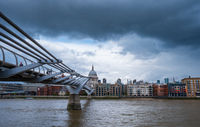 View of the Millennium Footbridge leading towards St Paul's Cathedral illuminated through an opening of a stormy sky.