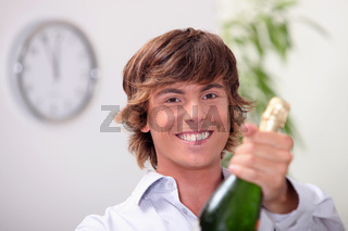 Young man with a bottle of champagne and a clock showing five to twelve