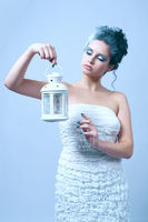 Beautiful woman with winter style makeup and lantern in hand