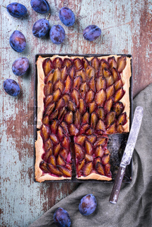 Traditional German Zwetschgenkuchen with sliced plums offered as top view on a rustic backing sheet on a wooden board