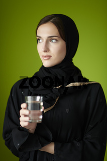 Middle eastern woman in abaya holding a glass of water