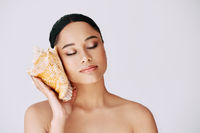 Pretty african american woman with closed eyes pressed conch seashell to her ear enjoy and dreams
