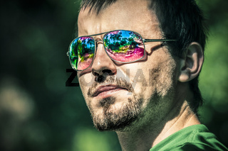 Man in sunglasses with colourful reflection