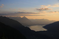 Golden evening sky over Lake Thun and mountain ranges.