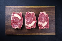 Modern style raw dry aged wagyu rib-eye beef steaks offered as top view on a wooden design board with copy space