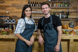 Portrait of smiling waiter and waitresses standing at counter