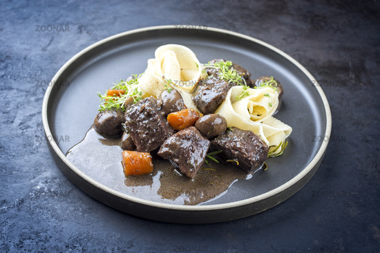 Modern style traditional French boeuf bourguignon with tagliatelle noodles in red wine sauce served as close-up in a Nordic design plate