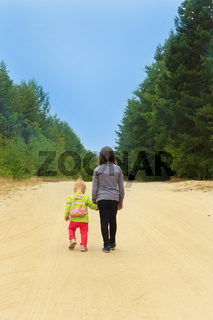 Little tourists go on road. Girls travellers walk on the forest path