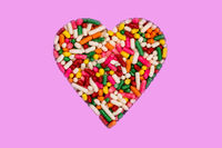 Heart shaped colorful rainbow sprinkles isolated on pink background.