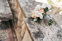 bridal bouquet of white and cream peonies, roses, salal, artemisia with pearl ribbon on the railing of an ancient staircase
