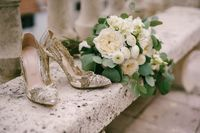 Elegant women's shoes with patterns on high heels on a bench with a wedding bouquet of white flowers.