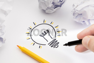 Bright Idea Concept. Hand Drawing Light Bulb On Paper and crumpled paper around. Creative process concept