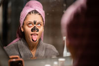 Beautiful woman with a clay or a mud mask on her face showing tongue