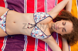 Overhead view of a beautiful woman napping on her colourful beach towel