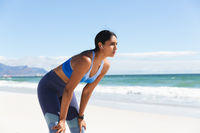 Mixed race woman exercising on beach wearing wireless earphones taking rest