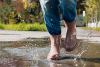 Woman wearing rain rubber boots walking running and jumping into puddle with water splash and drops in autumn rain