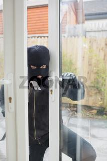 Burglar opening carefully the door