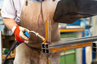 A metal worker welding and fabricating a metal frame for a garden patio