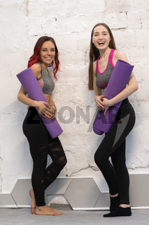 Two pretty fitness girls in sports out fits holding a yoga mat standing next to the white wall, smiling on camera isolated on wall background. Practicing in studio, working out indoor. Loft interior