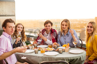 Cheerful friends drinking white wine during roof party