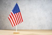 USA american table flag on white textured wall. Copy space for text, designs or drawings