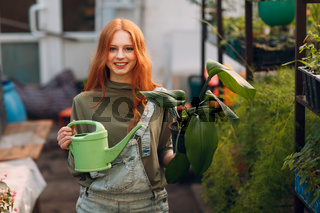 Home gardening concept. Young woman with green watering can planting plants floral in greenhouse garden at home.