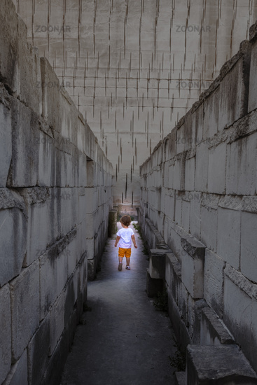 Caucasian young kid walking in a labyrinth. Conceptual image for dangerous situation during childhood.