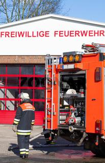 Feuerwehr Feuerwehrmann vor Einsatzfahrzeug