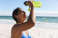 Mixed race woman exercising on beach wearing wireless earphones dousing with water